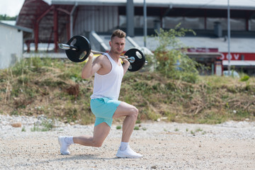Bodybuilder Exercising Legs With Barbell Outdoors