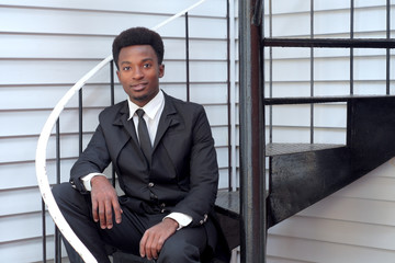 young man black suit and tie sitting stairs businessman professional