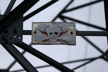 """A sign that reads """"Danger of death and High Voltage"""" is seen on an electrical tower in Santiago,"""