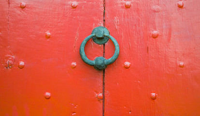 background texture weathered wooden red door panel with iron door knocker and nail decoration