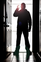 Man standing at door, in silhouette with flashlight