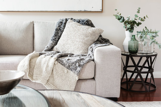 Textured layers interior styling of cushion sofa and throw in nuetral colors