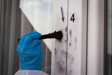 Female forensic expert find fingerprints on the window with help brush and black powder