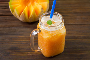 Tasty smoothies of melon  in a glass jar on a wooden background