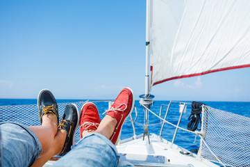 Two pairs legs in red and blue topsiders on white yacht deck. Yachting