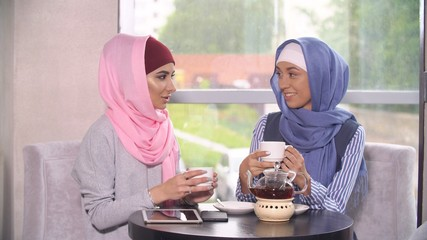 Two Beautiful Young Muslim Women in Cafe Communicate.