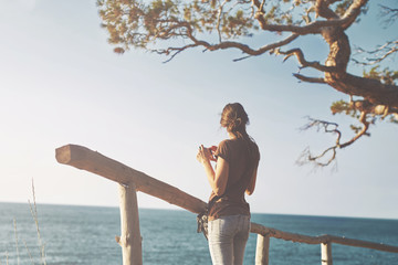 A woman stands near a wooden fence on the sea beach and takes pictures on a smartphone
