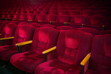 Red velvet armchairs in the empty auditorium