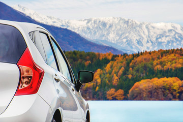 Road Trip Concept, Car Driving Travel in Autumn Season, Lake, beautiful Foliage and Mountains covered by Snow as background
