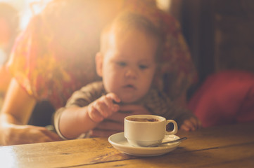 Baby reaching for cup of coffee