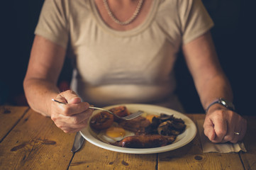 Senior woman eating english breakfast