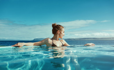 Young cheerful girl swimming in water of pool looking away on background of sea, Iceland, West Fjords.