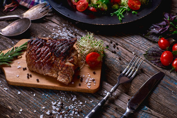Overhead view of colorful vegetables, savory sauces and salt served with grilled steak on a rustic wooden counter in a country steakhouse.Close-up