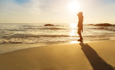 Beautiful golden sunrise in the sea. Reflection in the water. Woman standing on the beach.