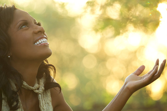 Excited African American woman with open arms.