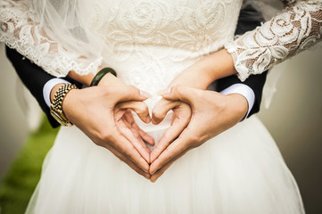 Couple After Marriage Forming Heart Symbol with their Hands