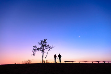 Silhouette of a lovely couple watching beautiful sunrise on the mountain.  Dawn light and beautiful sky with copy space. Romantic love of couple concept.