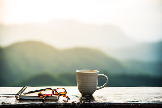 A coffee cup, eyeglasses and a note book on wooden table with sunrise and mountain  bokeh background. A start of new day with hot beverage. Business concept.