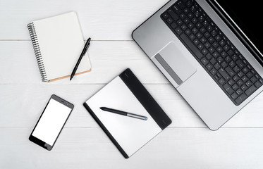 Top view on white wooden table with open blank laptop computer, cell phone, empty diary and graphic tablet, free space. Mobile phone with white screen, copy space