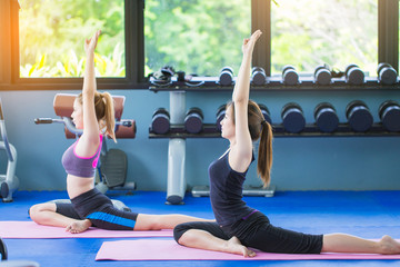 group of women doing Yoga in public fitness gym