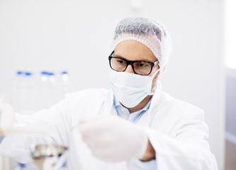 Close up portrait of male scientist with mask and glasses in laboratory.