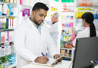 Chemist Writing On Clipboard While Colleagues Working In Pharmac