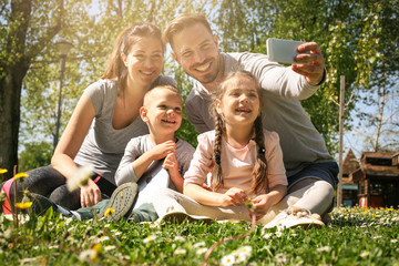 Happy family smiling while taking self-portrait  in park. Family enjoying in the spring day.