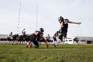Man holding ball while another sportsman kicking it during game of American football.