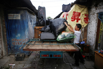 A man loads his belongings onto the flatbed of a tricycle as he moves out of his unit in a cluster of migrant dwellings that is slated for demolition at Dongsanqi village in the outskirts of Beijing