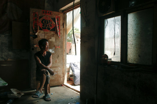 Zhu Xiangzhi smokes as he sits at the entrance to one of his two single-room units in a cluster of migrant dwellings that is slated for demolition at Dongsanqi village in the outskirts of Beijing