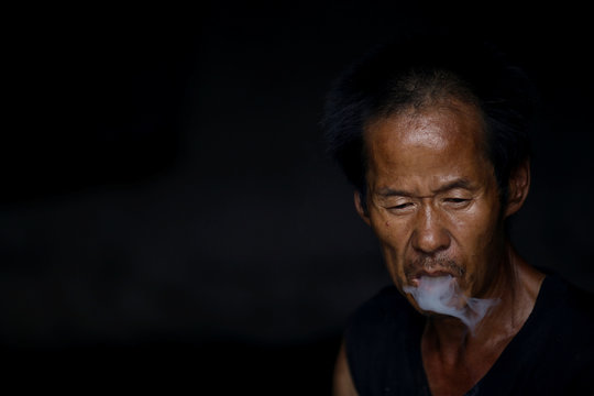Zhu Xiangzhi smokes as he sits at the entrance to one of his two single-room units in a cluster of migrant dwellings that is scheduled for demolition at Dongsanqi village in the outskirts of Beijing