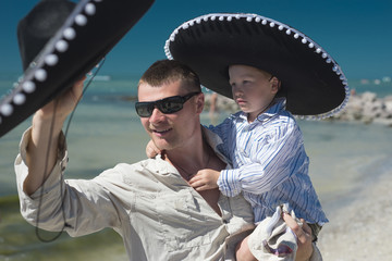 Father and son in a Mexican hat on the sea