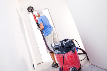 Worker polishes the wall. Plaster finishing float