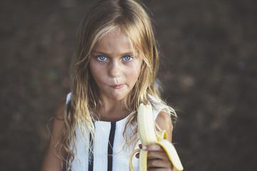 Girl eating banana outside