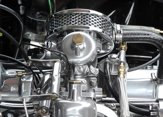 details of a shiny polished chome and steel vintage sports car engine