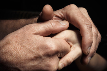Hands of an elderly man holding the hand of a younger man.