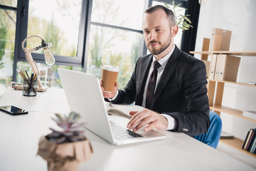 handsome young businessman using laptop with cup of coffee