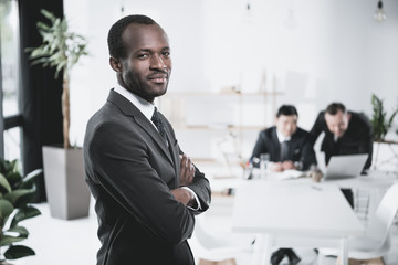 handsome young african-american businessman with folded arms