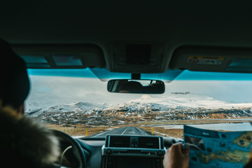 People traveling in car in iceland with a mountain in the background