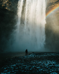 Person standing in front of Skogafoss waterfall in Iceland during sunset and rainbow