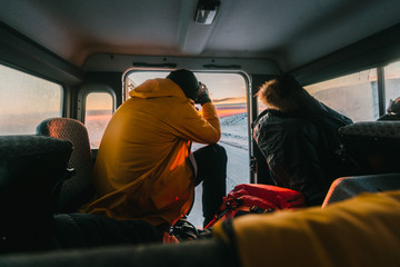Person photographing a sunset from the back of a car in iceland