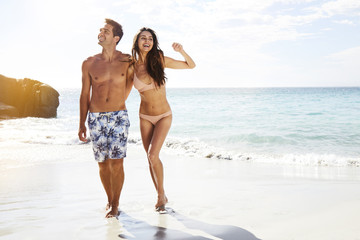 Good looking vacationing couple on beach, smiling