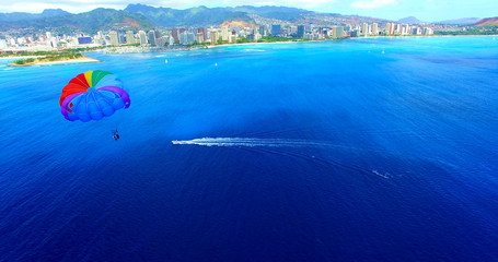 Parasailer With Rainbow Parachute Off The Coast of Honolulu/Waikiki Beach - Aerial Footage in Oahu, Hawaii