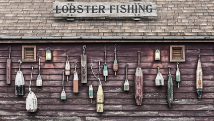 Closeup of colorful floats hanging outside a lobster fisherman's cottage. The image is weathered to add effect