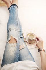 A young woman wearing distressed jeans sitting on wood floor on a white fur carpet at home and holds a cup of coffee in his hand. Gold bright feminine theme