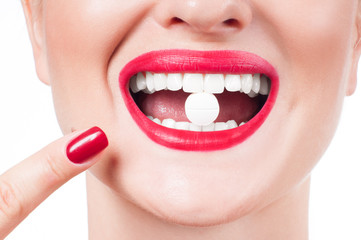 Female mouth with red lips and medicine pill