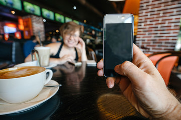 man is making a photo of a girl in a cafe on her smartphone. Hand of a man with a phone on the background of a girl and the interior of a cafe.