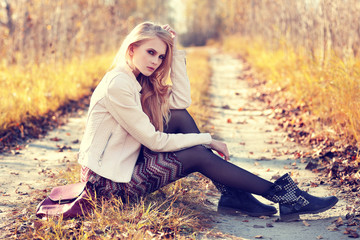 Fashion portrait of young woman outdoor in autumn.
