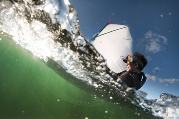 Over under close up image of a boy sailing an optimist class dinghy