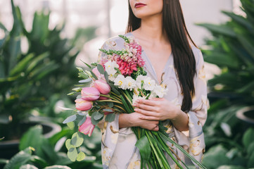 Young woman with long hair holding flowers bouquet